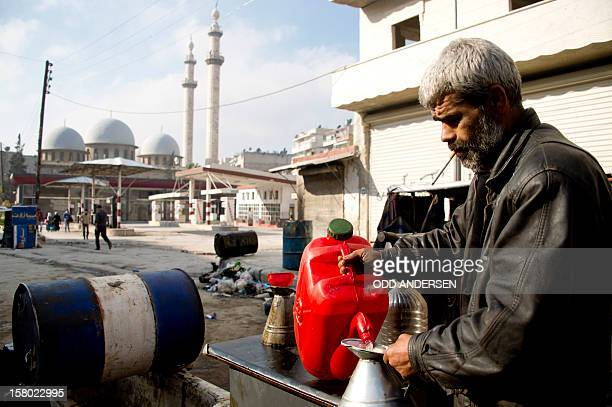 A Syrian man who set up up a business outside a destroyed petrol station pours petrol for sale into a can in the alFardos neighbourhood of the...