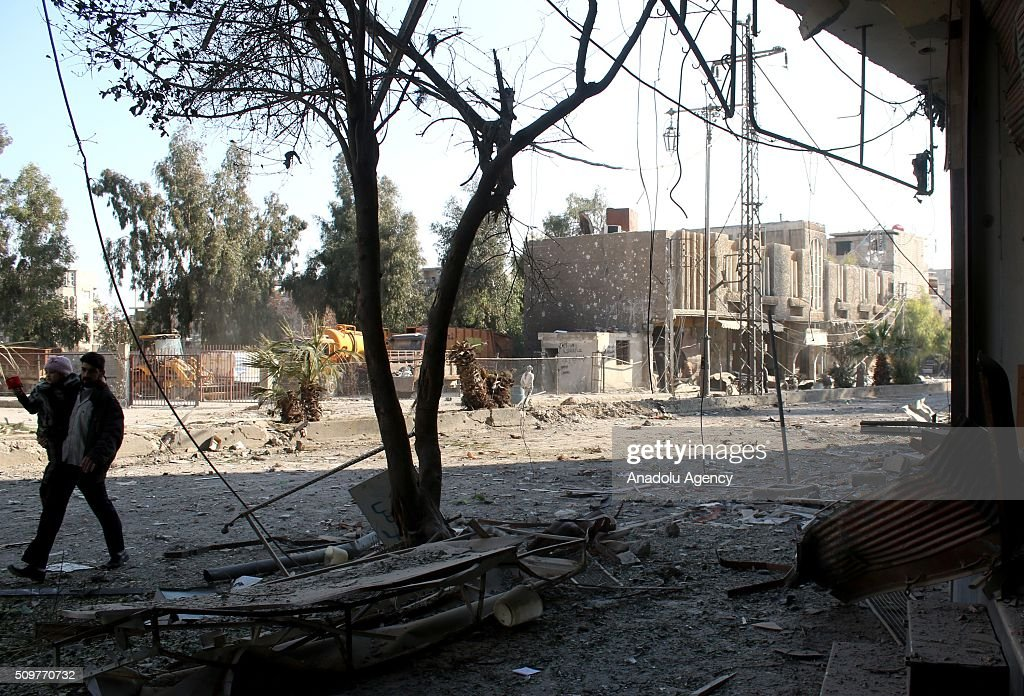 A Syrian man with his kid walk amid the debris of damaged buildings after Assad regime war crafts carried out an airstrike over Eastern Ghouta region in Damascus, Syria on February 12, 2016.