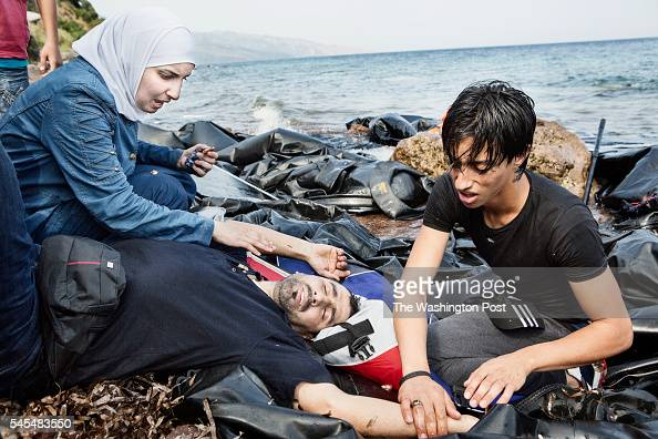Syrian man's wife and friend tend to him when he falls ill upon arriving after drinking too much sea water on August 1 2015 on the island of Lesvos...