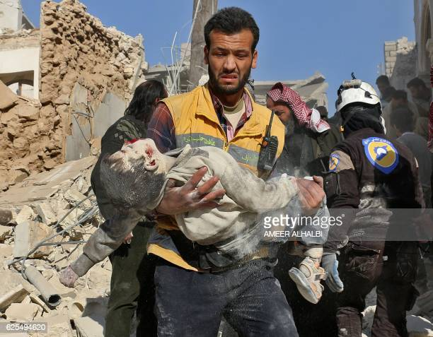 Syrian medic carries the body of a boy after it was retrieved from the rubble following a reported barrel bomb attack on the Bab alNairab...