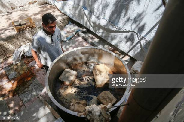 A Syrian member of the Adala Foundation a local NGO boils straw at a makeshift cultivation centre in the rebelheld town of Douma on the eastern...