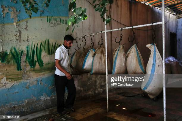 A Syrian member of the Adala Foundation a local NGO hangs boiled straw bags at a makeshift cultivation centre in the rebelheld town of Douma on the...