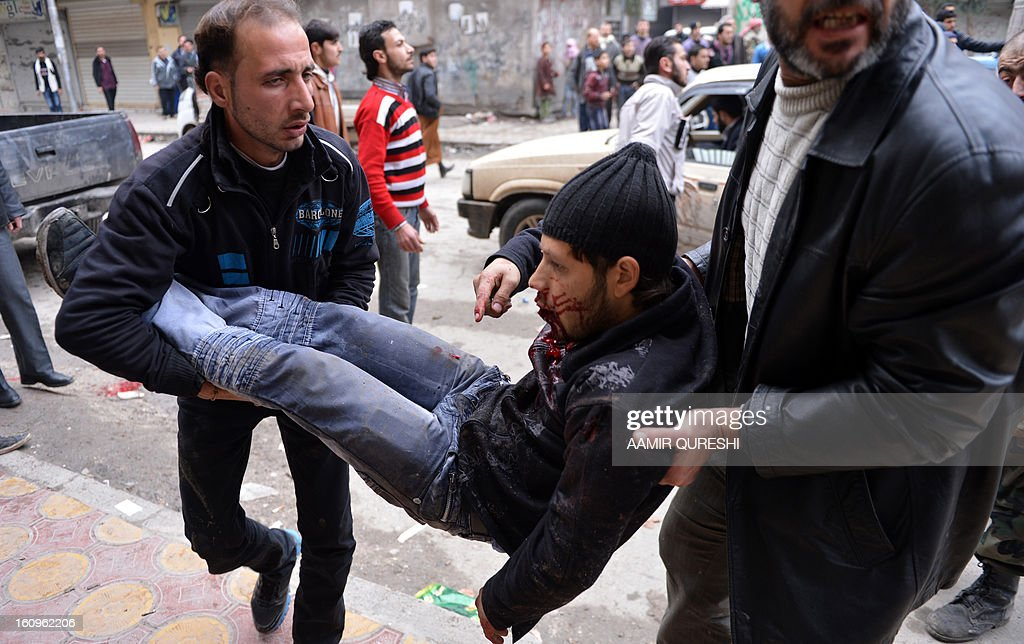 Syrian men carry an injured civilian upon his arrival at a hospital in the northern city of Aleppo on February 8, 2013, following shelling by government forces. Loyalists troops made ground in the country's north, retaking Karnaz on the strategic Damascus-Aleppo highway on Wednesday after a 16-day onslaught, said Rami Abdel Rahman, head of the Syrian Observatory for Human Rights.