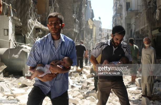 TOPSHOT Syrian men carrying babies make their way through the rubble of destroyed buildings following a reported air strike on the rebelheld Salihin...