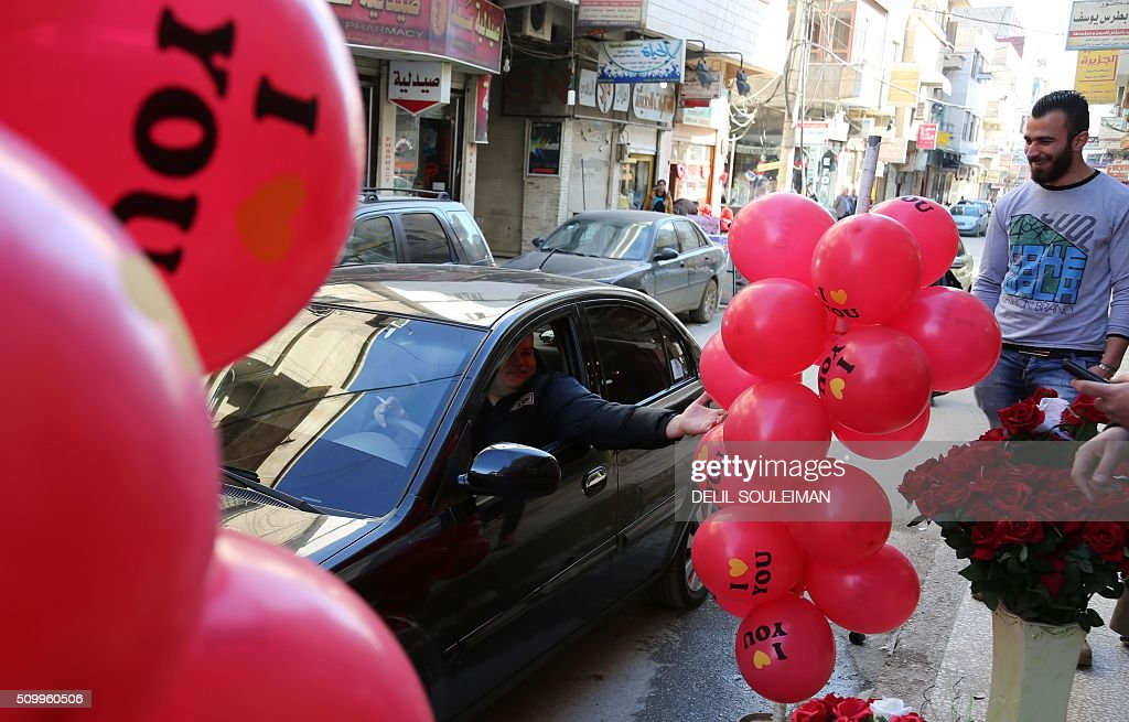 Syrian men chat outside a shop displaying Valentine's day gifts in the northeastern city of Qamishli on February 13, 2016. / AFP / DELIL SOULEIMAN