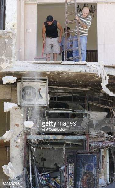 Syrian men clean up the damage at the site of a suicide bomb attack in the capital Damascus' eastern Tahrir Square district on July 2 2017 Syrian...