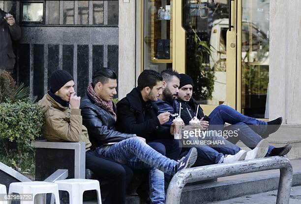 Syrian men drink coffee as they sit on a bench in a shopping district of the capital Damascus on January 29 2017 / AFP / Louai Beshara