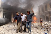 Syrian men help an injured person following a reported barrel bomb attack by Syrian government forces that hit an open market in the northern city of...