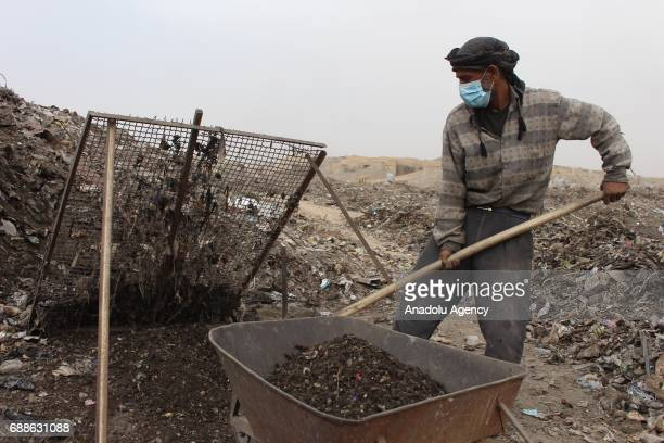 Syrian men including district council laborers collect waste to product organic fertilizer in Eastern Ghouta in Damascus Syria on May 22 2017 Farmers...