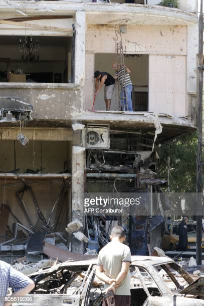 Syrian men inspect the damage at the site of a suicide bomb attack in the capital Damascus' eastern Tahrir Square district on July 2 2017 Syrian...