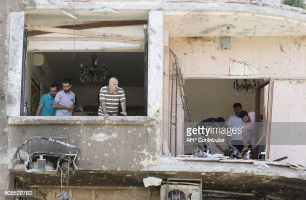 Syrian men inspect the damage inside a building at the site of a suicide bomb attack in the capital Damascus' eastern Tahrir Square district on July...
