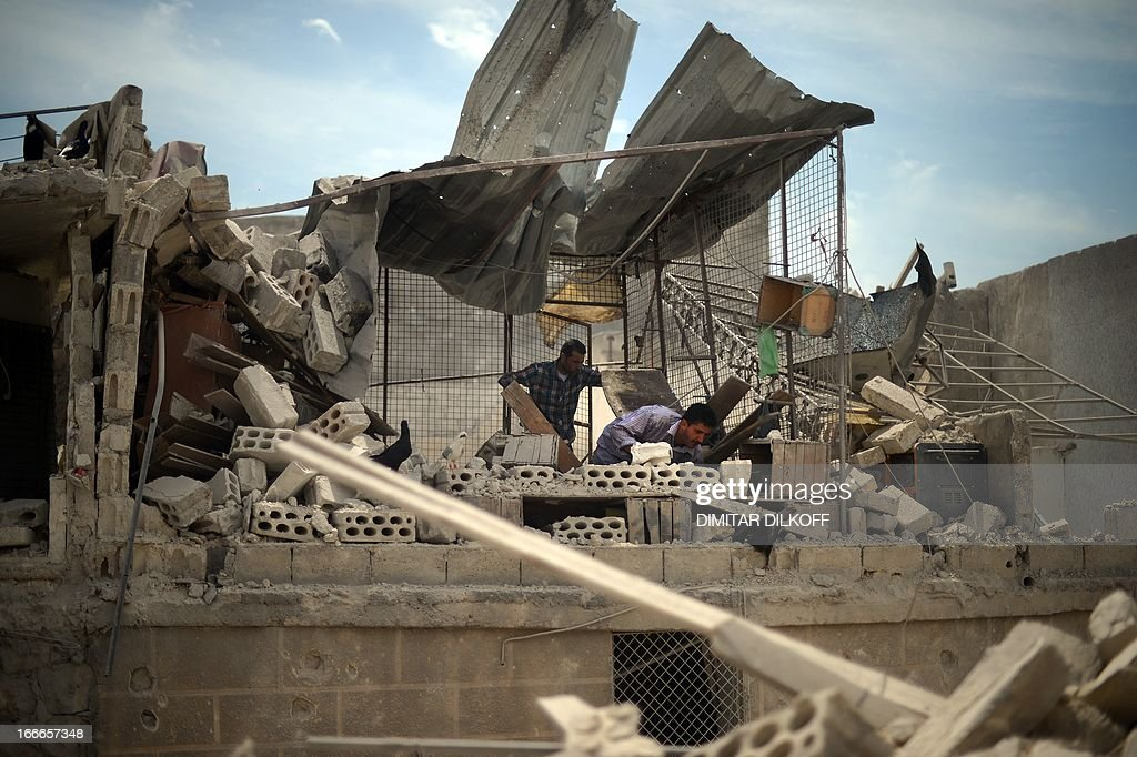 Syrian men inspect the remains of their destroyed house following an airstrike by the Syrian airforce in the northern Syrian city of Aleppo on April 15, 2013. The conflict in Syria, which is now in its third year, has cost 70,000 lives, according to the United Nations.
