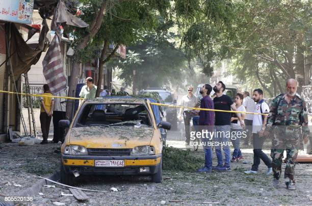 Syrian men look at a cordoned off area at the site of a suicide bomb attack in the capital Damascus' eastern Tahrir Square district on July 2 2017...