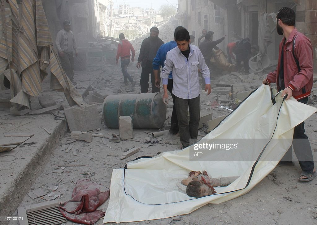 Syrian men pick up the remains of a body following a reported air strike by Syrian government forces on March 7, 2014 during the Friday prayer in the Sukkari neighborhood of the northern city of Aleppo. More than 140,000 people have been killed in Syria since the start of a March 2011 uprising against the Assad family's 40-year rule.