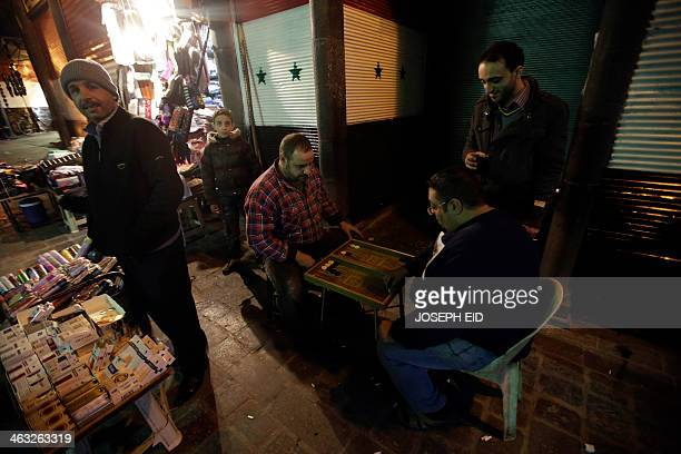 Syrian men play backgammon outside a shop whos shutters are painted with the Syrian national flag's colours at alHamidiyah market in old Damascus on...