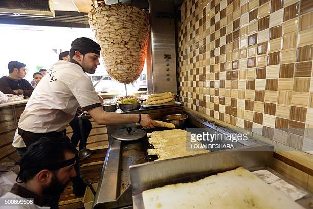Syrian men prepare shawarma sandwiches a popular Middle Eastern dish of grilled spiced meat at a restaurant in the capital Damascus on December 10...