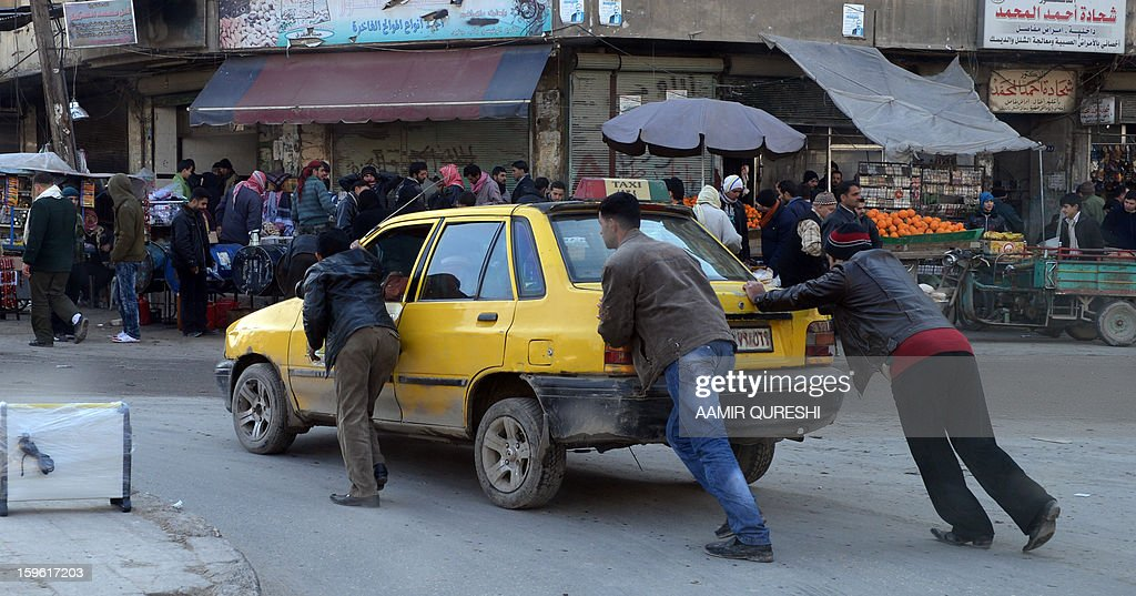 Syrian men push a taxi in Aleppo's old city on January 17, 2013. Rebels trying to break a months-long deadlock in their battle for Syria's second city Aleppo say they are cutting supply routes ahead of simultaneous assaults on regime bases. AFP PHOTO/AAMIR QURESHI