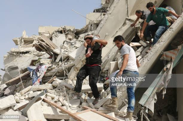 Syrian men remove a baby from the rubble of a destroyed building following a reported air strike in the Qatarji neighbourhood of the northern city of...