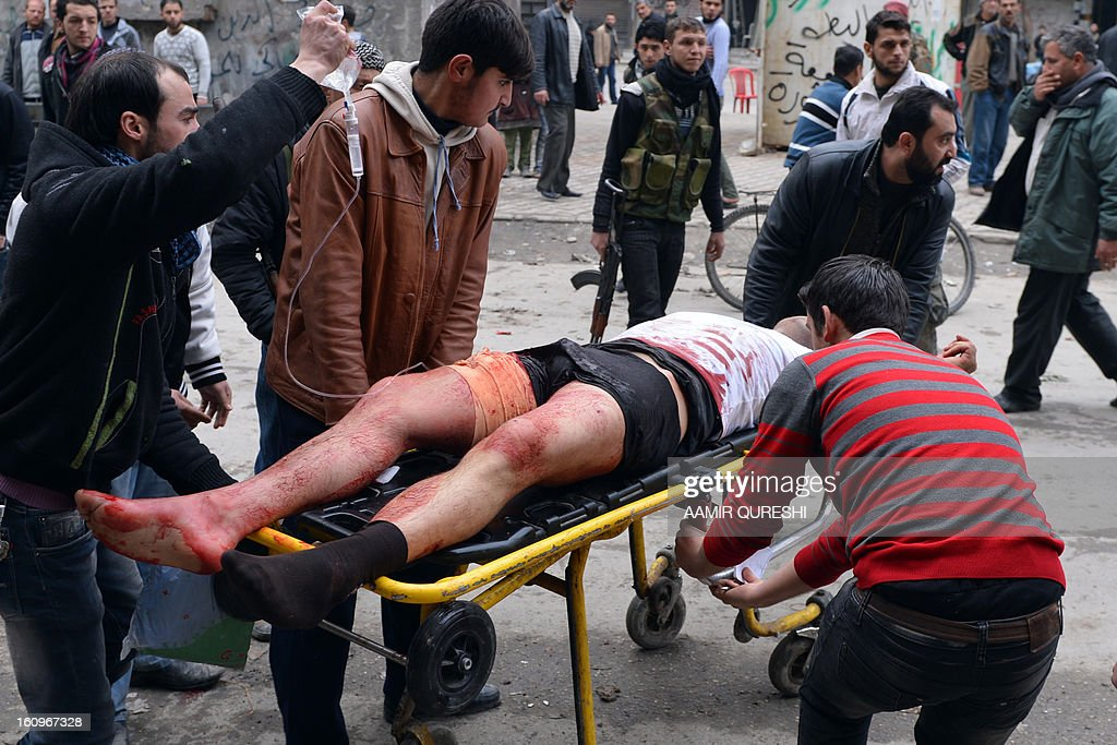 Syrian men rush a wounded civilian to hospital in the northern city of Aleppo following shelling by government forces on February 8, 2013. Syrian forces shelled rebel belts, the Syrian Observatory for Human Rights said, as an army offensive raged into a third straight day.