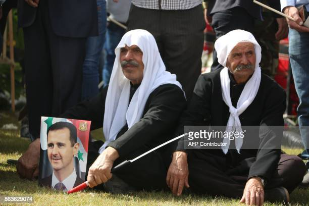 Syrian men sit on a lawn next to a picture of President Bashar alAssad as they gather at a stadium to attend the funeral of Brigadier General Issam...