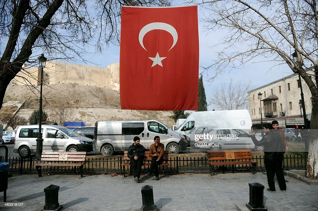 Syrian men sit under a Turkish flag on January 17 2014 in Gaziantep southern Turkey UN refugee chief Antonio Guterres said on January 17 it was vital...