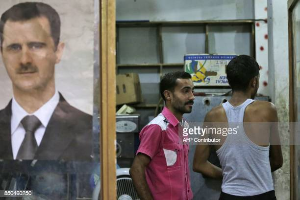 Syrian men stand at a shop decorated with a portrait President Bashar alAssad in the eastern city of Deir Ezzor on September 20 2017 as Syrian...