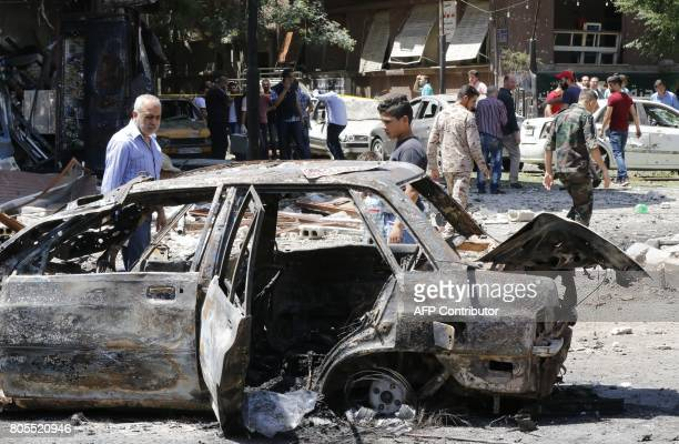 Syrian men stand next to a charred vehicle as they inspect the damage at the site of a suicide bomb attack in the capital Damascus' eastern Tahrir...