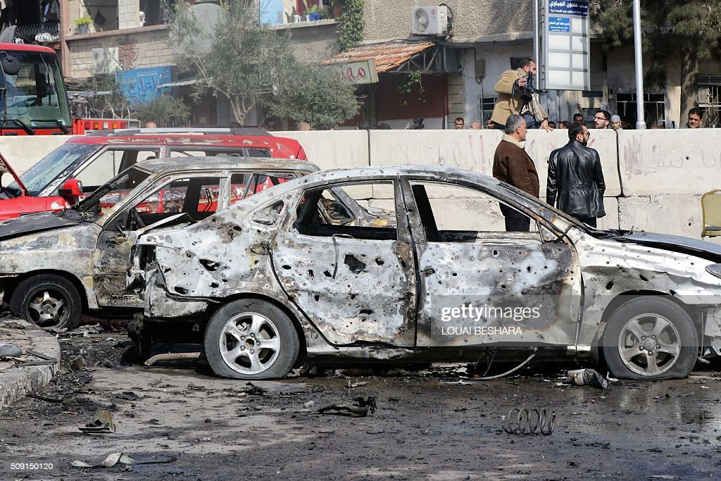 Syrian men stand next to a damaged car at the site of a suicide attack at a police officer's club in the Masaken Barzeh district of the capital Damascus on February 9, 2016. The Syrian Observatory for Human Rights said about 20 people had also been wounded, adding that policemen were among the dead and injured. BESHARA