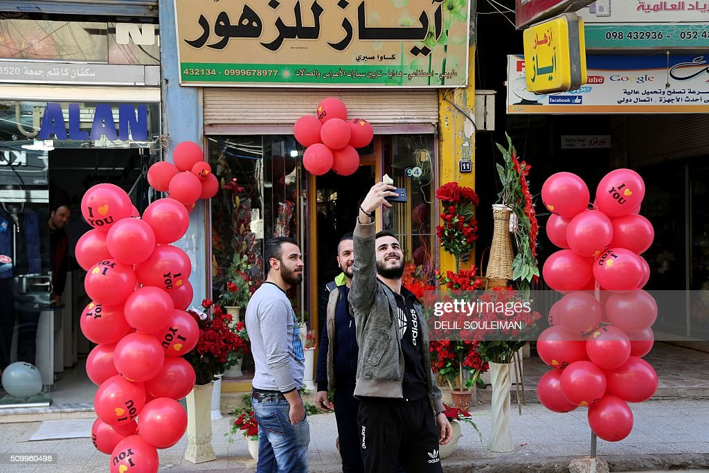 Syrian men take a selfie in front of a shop displaying Valentine's day gifts in the northeastern city of Qamishli on February 13, 2016. / AFP / DELIL SOULEIMAN