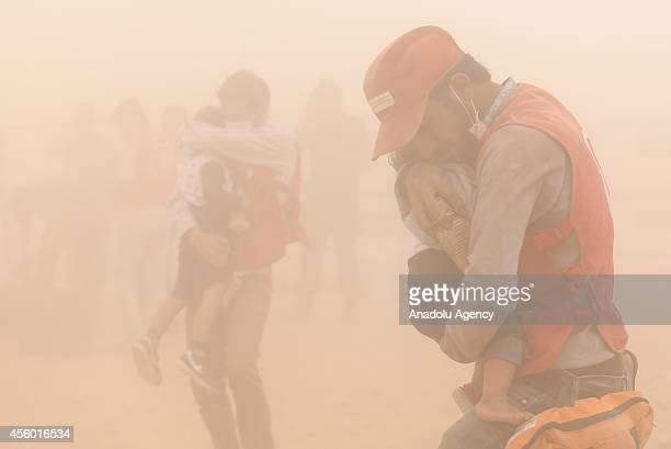 Syrian men try to protect their children during the sandstorm that hit Suruc district of Sanliurfa Turkey on September 24 2014 A powerful sandstorm...