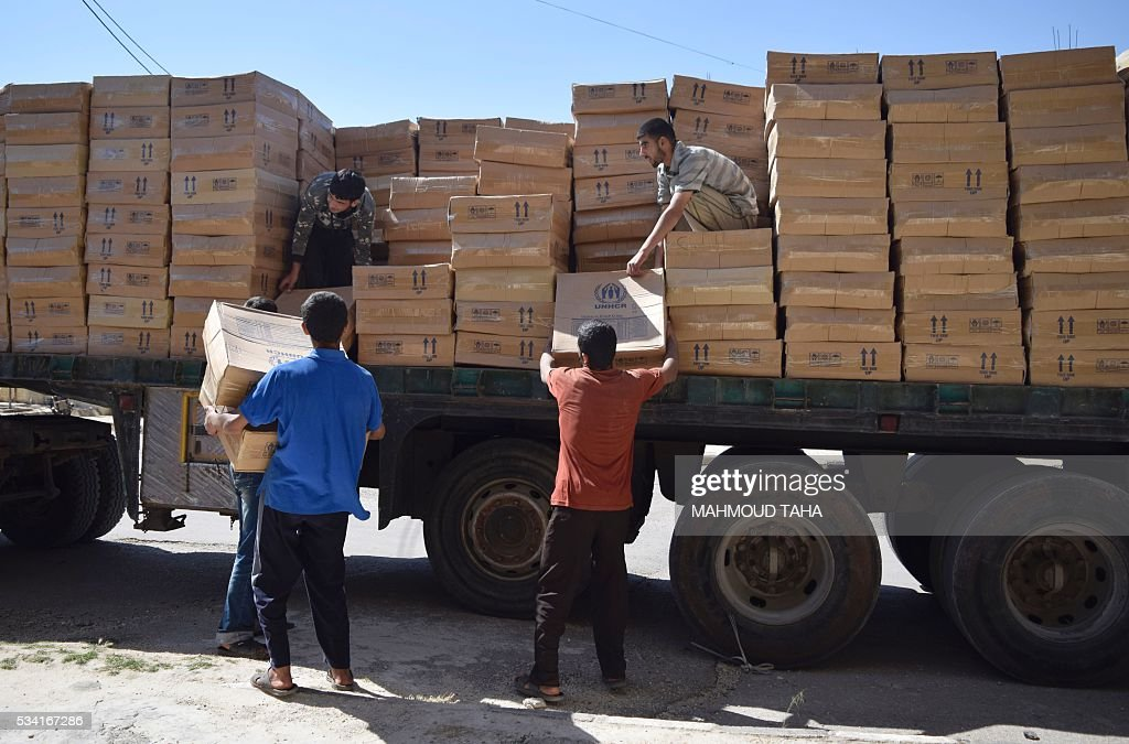 Syrian men unload aid parcels provided by the UN World Food Programm (WFP) and the Syrian Arab Red Crescent in the rebel-held town of Al-Houla, on the northern outskirts of Homs in central Syria, on May 25, 2016. / AFP / MAHMOUD