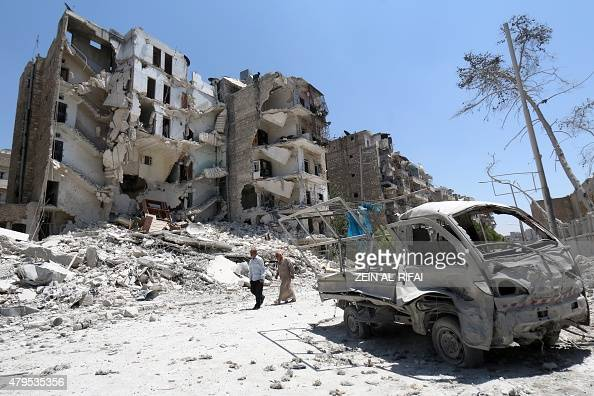 Syrian men walk amidst the rubble and debris in the Qadi Askar district of the northern Syrian city of Aleppo on July 5 2015 Two alliances of Syrian...