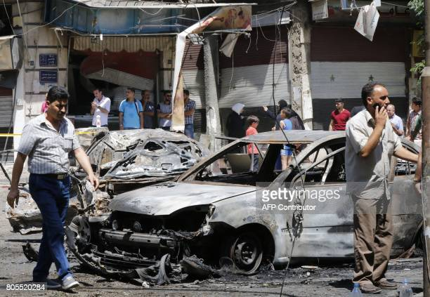 Syrian men walk past charred vehicles at the site of a suicide bomb attack in the capital Damascus' eastern Tahrir Square district on July 2 2017...