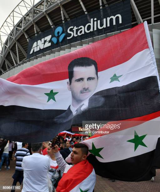 Syrian migirants carry their national flags and pictures of Syrian President Bashar alAssad jubilate outside the stadium prior to 2018 World Cup...