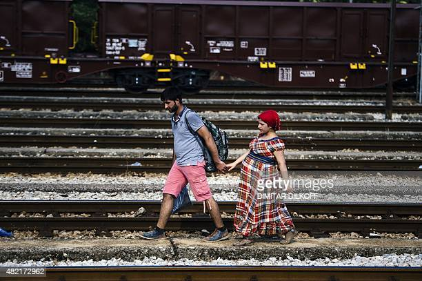 A Syrian migrant and his pregnant wife walk on train tracks towards the town of Gevgelija on July 27 on the MacedonianGreek border trying to catch a...