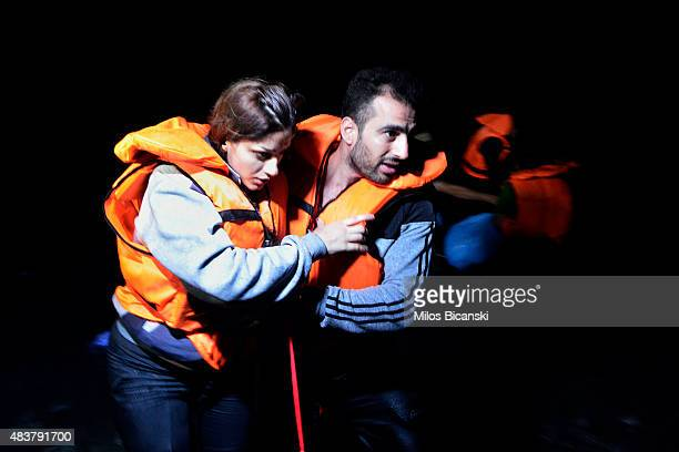 Syrian migrant couple help eaach other as they arrive at a beach on the Greek island of Kos after crossing a part of the Aegean sea from Turkey to...