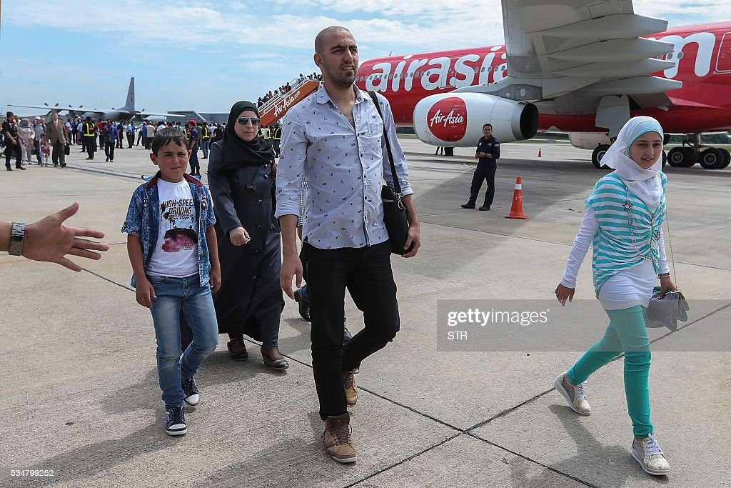 A Syrian migrant family arrives at Subang Air Force base in Subang, outside Kuala Lumpur on May 28, 2016. Malaysia on May 28 received 68 Syrian refugees including 31 children out of a total of 3,000 it hopes to allow into the predominantly Muslim country with hundreds more expected soon. / AFP / STR / Malaysia OUT
