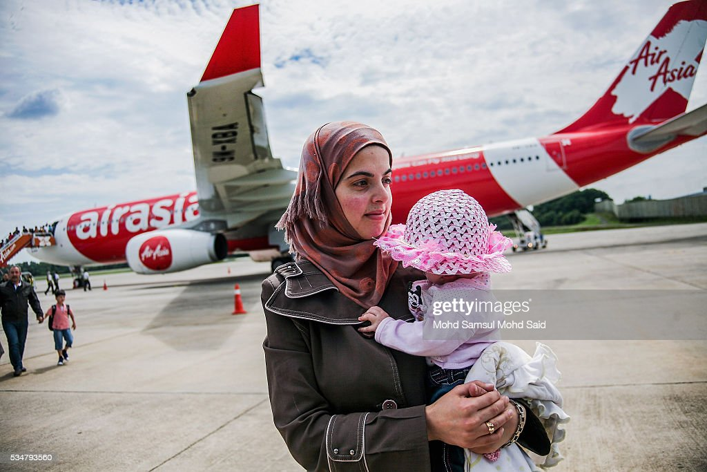 A Syrian migrant from the Bekka Valley refugee camp in Lebanon, carries her daughter upon arriving at the Royal Malaysian Air Force (RMAF) Base on May 28, 2016 in Subang Jaya, Malaysia. Malaysia has received almost 68 Syrian immigrants that have been selected to join this migrant program. Prime Minister Najib Razak has announced at the 70th United Nations Assembly that Malaysia would open its doors to 3,000 Syrian refugees in three years to help in the refugee crisis.