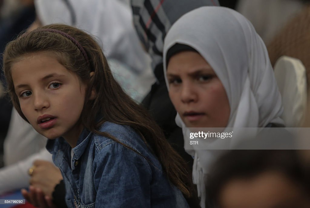Syrian migrant girls look on after arriving at Subang Air Force base in Subang, outside Kuala Lumpur on May 28, 2016. Malaysia on May 28 received 68 Syrian refugees including 31 children out of a total of 3,000 it hopes to allow into the predominantly Muslim country with hundreds more expected soon. / AFP / STR / Malaysia OUT