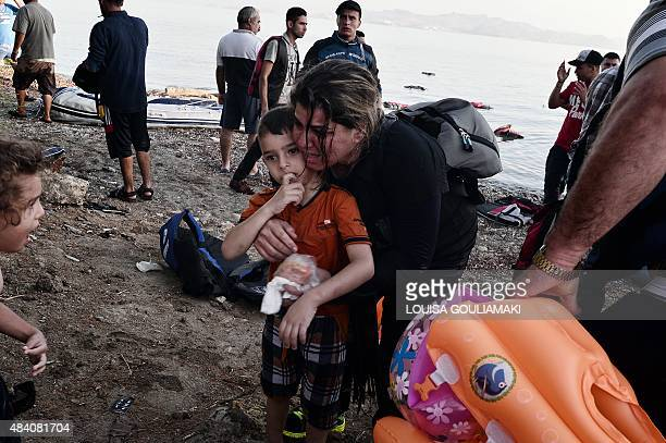 A Syrian migrant holds her son as she arrives on an overcrowded dinghy on a beach near the port on the Greek island of Kos on August 15 2015 A ferry...