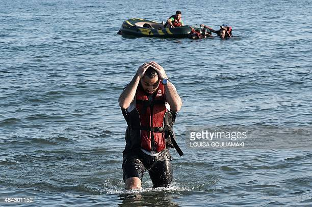A Syrian migrant reacts after reaching the shores of the Greek island of Kos on August 17 2015 Their small engine broke down and they made it...