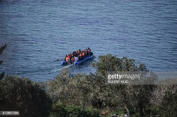 Syrian migrant sit in a dinghy as they attempt to cross the Aegean Sea to the Greek island of Lesbos from the Ayvacik coast in Canakkale on February...