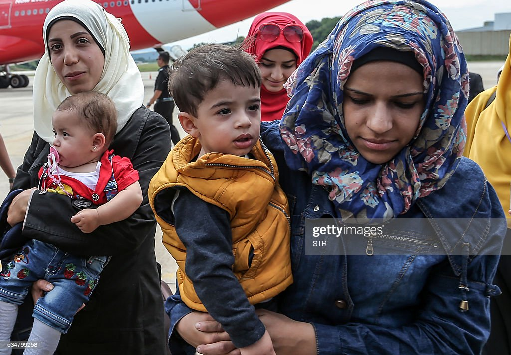 Syrian migrant women carry their children as they arrive at Subang Air Force base in Subang, outside Kuala Lumpur on May 28, 2016. Malaysia on May 28 received 68 Syrian refugees including 31 children out of a total of 3,000 it hopes to allow into the predominantly Muslim country with hundreds more expected soon. / AFP / STR / Malaysia OUT