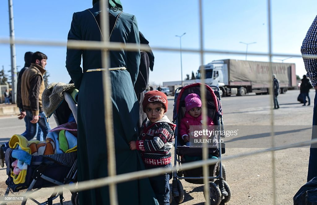 Syrian migrants and refugees wait in front of the Turkish Oncupinar crossing gate, near the town of Kilis, to return to Syria on February 9, 2016. Around 30,000 Syrians are at the Turkish border after fleeing a Russia-backed regime offensive on the northern region of Aleppo, Turkish Prime Minister Ahmet Davutoglu said on February 8, as his country faces mounting pressure to open its border. Davutoglu said the refugees would be admitted if need be, although Turkey should not be expected 'to shoulder the refugee issue alone.'. / AFP / BULENT KILIC