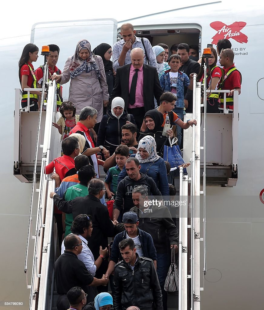 Syrian migrants arrive at Subang Air Force base in Subang, outside Kuala Lumpur on May 28, 2016. Malaysia on May 28 received 68 Syrian refugees including 31 children out of a total of 3,000 it hopes to allow into the predominantly Muslim country with hundreds more expected soon. / AFP / STR / Malaysia OUT