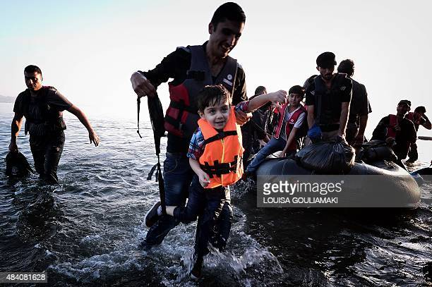 Syrian migrants arrive on an overcrowded dinghy on a beach near the port on the Greek island of Kos on August 15 2015 A ferry boat has been sent by...