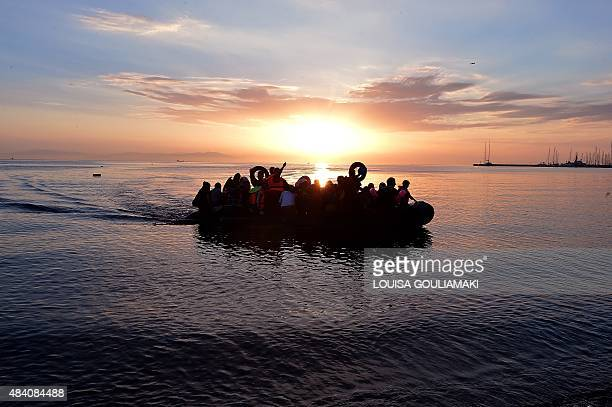 Syrian migrants arrive on an overcrowded dinghy to the coast of the southeastern Greek island of Kos from Turkey on August 15 2015 A ferry boat has...