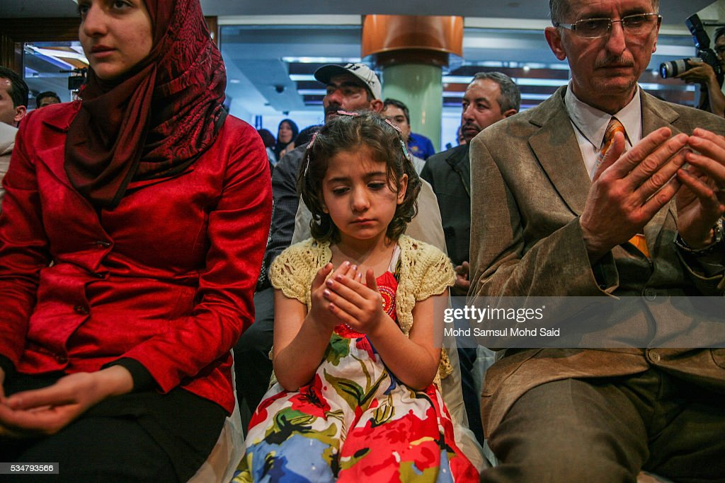 Syrian migrants, from the Bekka Valley refugee camp in Lebanon, pray upon arrival at the Royal Malaysian Air Force (RMAF) Base on May 28, 2016 in Subang Jaya, Malaysia. Malaysia has received almost 68 Syrian immigrants that have been selected to join this migrant program. Prime Minister Najib Razak has announced at the 70th United Nations Assembly that Malaysia would open its doors to 3,000 Syrian refugees in three years to help in the refugee crisis.