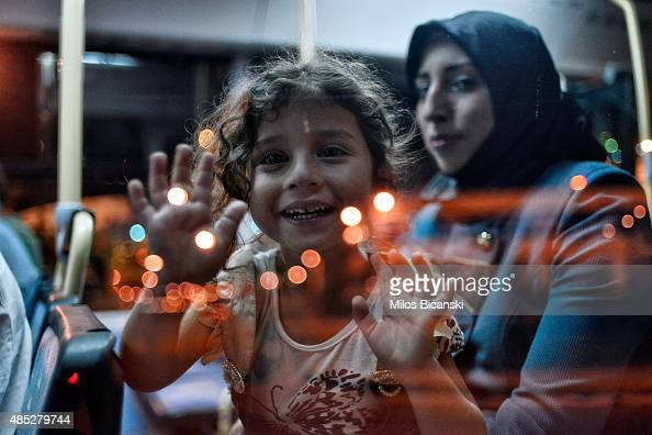 Syrian migrants travel on a bus after arriving on a ferry carrying about 2500 migrants from the Greek islands to the main port of Piraeus on August...