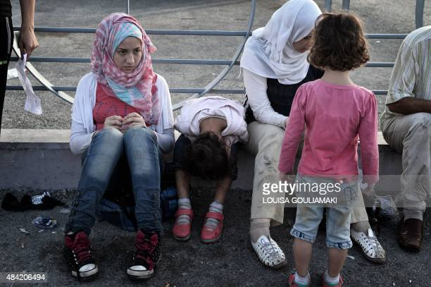 Syrian migrants wait to enter the port to board the Eleftherios Venizelos liner which will serve as their registration and for some housing facility...